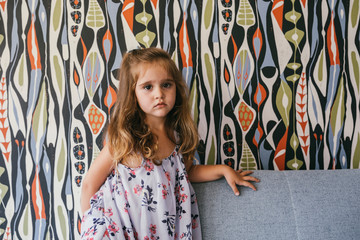 Portrait of serious little girl on couch in front of patterned wallpaper