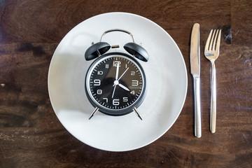 Intermittent fasting, trend : fasten, alarm clock on plate