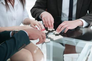 closeup .business team assembling puzzle sitting behind a Desk