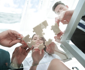 bottom view. business team folding puzzle pieces. .