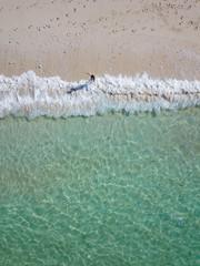 Indonesia, Bali, Melasti, Aerial view of Karma Kandara beach, woman going into water