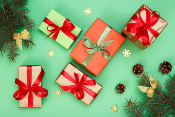 Gift boxes, fir tree branches with cones on green background