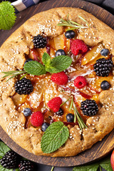 Whole-grain galette with plums and berries on dark background, top view