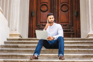 Young East Indian American College Student with beard studying in New York, wearing white shirt, blue pants, sitting on stairs outside on campus, working on laptop computer, talking on cell phone..