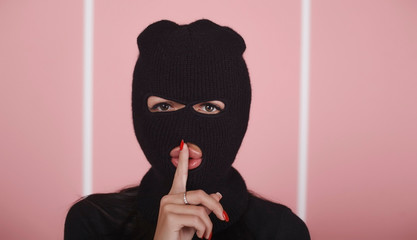 The girl in balaclava gives a gesture of silence