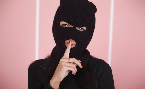 Portrait of a girl in a balaclava.  Holds a finger near the mouth