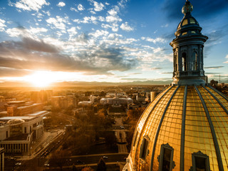 Aerial/Drone photograph of a sunset over the Colorado state capital building.  Capital city of Denver.  The Rocky Mountains can be seen on the horizon