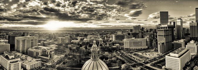 Aerial/Drone panorama of the capital city of Denver, Colorado at sunset.  The Rocky Mountains can be seen on the horizon
