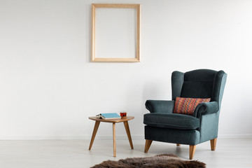 Empty wooden frame on white wall of stylish living room with comfortable armchair with patterned pillow, dark fury carpet and small table with book and tea