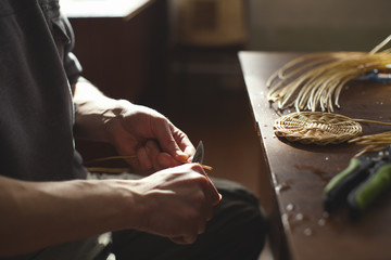 Obraz Basketwork from willow twigs in the workshop. Sharpening willow twigs. - fototapety do salonu
