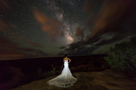 Bride posing under the Milky Way stars in the Utah desert.