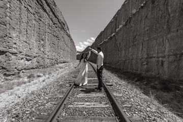 Bride and groom posing on the barren railroad tracks of the Utah desert, near Moab.