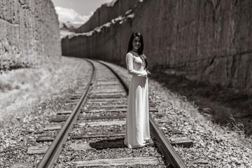 Vietnamese/Asian Bride in her traditional wedding dress.  Posing on the barren railroad tracks of the Utah desert, near Moab.