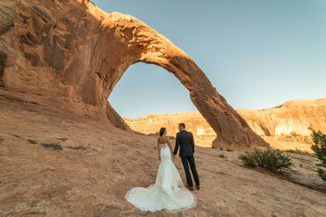 Asian/Vietnamese Bride with her Caucasian Groom.  Wedding/Engagement photo under the beautiful Corona Arch at sunset in the Utah desert near Moab.