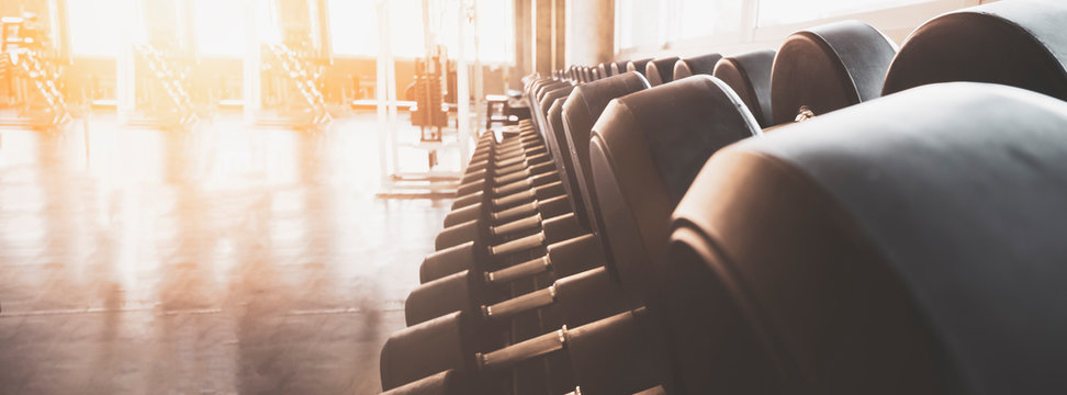 Gym equipment wide interior gym for fitness banner background close up dumbbells and blurred equipment