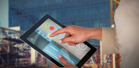 Composite 3d image of businesswoman using digital tablet