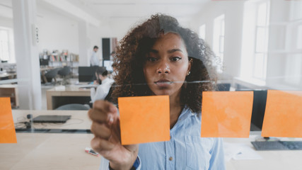 African American black employee looking onto a glass wall with sticky notes, framework for managing work, scrum methodology