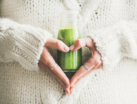 Winter seasonal smoothie drink detox. Female in woolen sweater holding bottle of green smoothie or juice making heart shape with her hands. Clean eating, weight loss, healthy dieting food concept