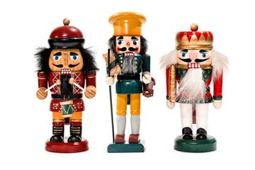 Merry Christmas: Three traditional colorful vintage wooden nutcracker puppets in uniform isolated on white background and copyspace for text - concept festive Christmas decoration ornament dolls