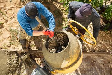 Workers pour concrete solution at a construction site