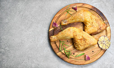 Delicious roast chicken legs or chicken drumsticks on a wooden cutting board. High angle view and fresh rosemary and garlic. Closeup shot, top view.