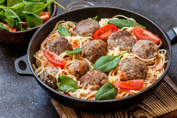 meat balls with pasta spaghetti with spinach, fresh tomatoes in a frying pan on a cutting Board