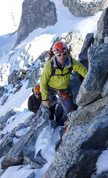 mountain guide leading male client to the summit of a high alpine peak on a beautiful summer day