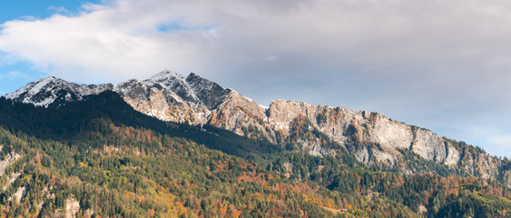 Wall Mural - panorama view of snow-capped mountain peaks and fall foliage color forest in the Maienfeld region of Switzerland