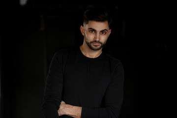 Handsome young businessman man with haircut and beard in black t-shirt stands on black background