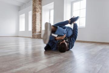Young male dancer in fashionable denim dress dancing in studio on the floor