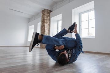 Man dancer in fashion denim clothes dancing in studio
