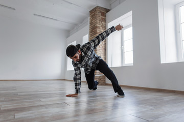 Young beautiful stylish dancer man with a cap and casual dress dancing break dance in the hall
