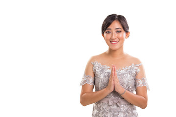 Warm greeting of young attractive ethnic Southeast Asia female model wearing traditional formal outfit posing with both palms clapping, over white background