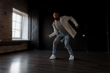 Young professional hip-hop dancer in white jacket and fashionable ripped jeans dancing against a dark background in the studio