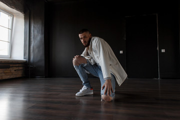 Stylish handsome young model man in fashionable clothes with a jacket and torn blue jeans with sneakers posing in a dark room.