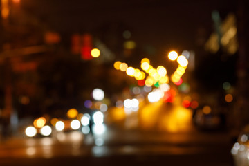 The blurred background of bright dipped headlamps with the illuminated night city landscape behind.