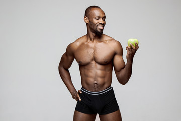 Fit young man with beautiful torso with green apple isolated on gray background. The naked torso of African American man posing at studio. The body, fitness, sports, healthy lifestyle and bodybuilder