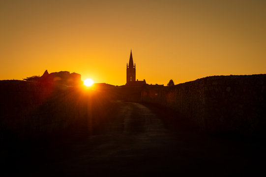 Beautiful sunrise on the steeple of the church and village of Saint Emilion, Religion, Gironde
