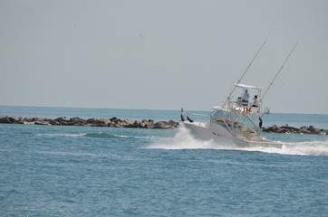 Sport fishing boat exiting Government Cut on its way to one ocean off of Miami Beach,Florida