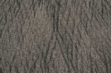 Wet black volcanic sand beach pattern and texture