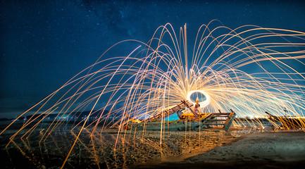 Phuket Steel wool fire on night beach.