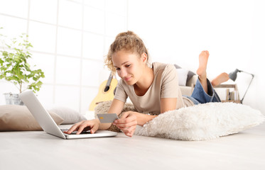 Young woman holding credit card and using laptop computer. Online shopping concept, Lying on living room wooden floor in modern white home with copy space