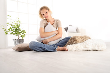 home concepts, young woman hugging a big comfortable cushions, sitting on the wooden floor of a modern living room, copy space template