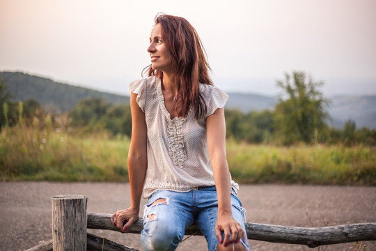 Beautiful happy woman sitting on a wooden fence in nature by the road
