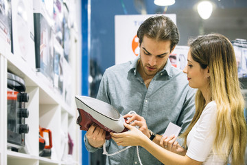 Young woman and man choosing a steam iron in an appliance store