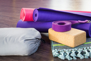 Variety of yoga props on wooden floor in studio. Pink and purple rolled mats, cork brick, belt,...