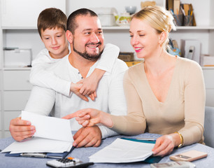 Happy parents with son looking at documents