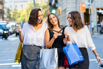 Threesome girl friends having fun shopping in city.