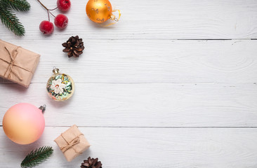 Christmas composition, gift boxes, fir branches and cones, ball, small red apples. Christmas toys on a white background, top view