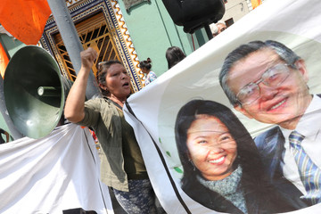 Supporters of opposition leader Keiko Fujimori hold a picture of her and her father, former President Alberto Fujimori, as they wait outside court where she is attending a hearing, in Lima